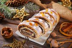 Sliced christmas poppy seed cake with icing and snowflake sprink Stock Image