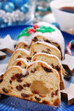 Sliced christmas stollen cake on blue plate Royalty Free Stock Images