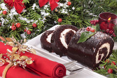 Sliced Christmas yule log cake on plate with napkin under tree Stock Photography