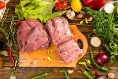 Sliced chunks of raw meat on cutting board. Sliced chunks of red raw meat on cutting board over wood grain table with various fresh greens and herbs surrounding Royalty Free Stock Photo