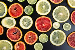 Sliced citrus fruits on a dark background pattern. Sliced citrus fruits on a dark background making pattern lemon orange lime grapefruit vegetarian black top stock images