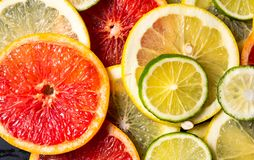 Sliced citrus fruits on a dark background pattern. Sliced citrus fruits on a dark background making pattern lemon orange lime grapefruit vegetarian black top stock image
