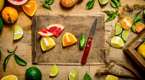 Sliced citrus fruits - grapefruit, orange, tangerine, lemon, lime on the old Board with box. Royalty Free Stock Photos