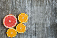 Sliced citrus fruits orange, grapefruit over wooden background Royalty Free Stock Image