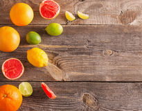 sliced citrus fruits over wooden background Royalty Free Stock Photography