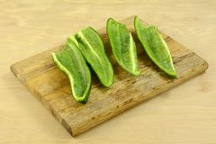 Sliced and cleaned poblano pepper. On wooden cutting board on wood table stock photo
