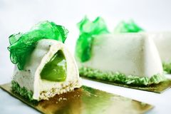 Sliced coconut water mousse dessert with green grapes and shiny green caramel decoration royalty free stock photography