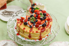 Sliced Crape Cake on top with Mixed Berries and Strawberry Sauce Stock Image