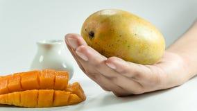 Sliced cube of fresh mango and one mango on hand. royalty free stock photos