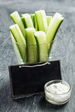 Sliced cucumber batons or crudites. Served with a small bowl of creamy savory vinaigrette sauce and a blank school slate with copyspace Royalty Free Stock Photo