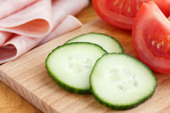 Sliced cucumber on chopping board with ham Royalty Free Stock Image