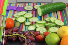 Sliced cucumber on colorful chopping board in kitchen Stock Photo