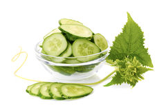 Sliced cucumber in glass bowl vith leaves on white Royalty Free Stock Images