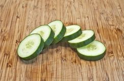 Sliced cucumber in half circle on cutting board Stock Images