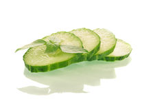 Sliced cucumber with a mint sprig. Sliced and whole  green cucumbers on white background Stock Image