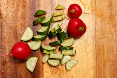 Sliced cucumber and radish on a wooden board. Fresh radishes and cucumber on a wooden board Royalty Free Stock Image