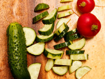 Sliced cucumber and radish on a wooden board. Fresh radishes and cucumber on a wooden board Royalty Free Stock Images