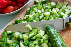 Sliced cucumbers and knife. Sliced cucumbers on the cutting board and knife, in the background the tomatoes in a bowl royalty free stock photo