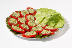 Sliced cucumbers and stuffed tomato salad. Vegetarian cuisine - cucumbers and stuffed with cheese tomato salad on plate Royalty Free Stock Images