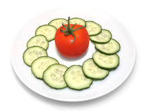 Sliced cucumbers and tomato on white plate. Sliced cucumbers in circle with tomato in the middle on white plate on white background Stock Images
