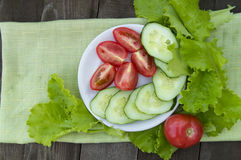 Sliced cucumbers and tomatoes with lettuce on old wooden table Stock Image