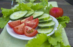 Sliced cucumbers and tomatoes with lettuce on old wooden table Royalty Free Stock Image