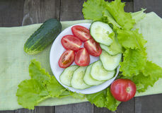 Sliced cucumbers and tomatoes with lettuce on old wooden table Royalty Free Stock Photography
