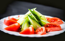 Sliced cucumbers and tomatoes and vegetables on a plate Royalty Free Stock Photos