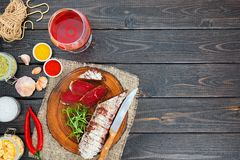 Sliced cured bresaola with spices and a glass of red wine. Royalty Free Stock Photos
