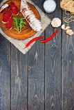 Sliced cured bresaola with spices and a sprig of rosemary. Stock Photography