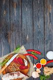 Sliced cured bresaola with spices and a sprig of rosemary. Royalty Free Stock Photography