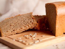 Sliced dark bread with crumbs on sacking background Royalty Free Stock Image