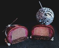 Sliced dark chocolate berry dessert with silver wool ball decoration and brownie stock photography