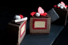 Sliced dark chocolate textured cube dessert with strawberry and vanilla insertion decorations and red sponge royalty free stock images