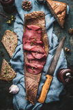 Sliced Deer meat ham with nut bread served on bark of tree with kitchen knife Royalty Free Stock Photography