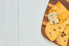 Sliced delicious cheese on wooden board. Slices of different types of cheese on kitchen board and copy space royalty free stock images