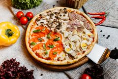 Sliced delicious tasty pizza with vegetables on wooden table. royalty free stock photography