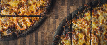 Sliced dough black pizza on the wooden table wide screen. Sliced dough black pizza on the wooden table top view wide screen Royalty Free Stock Photo