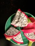 Sliced dragon fruit on a green plate and dark background. Slices of red-and-white dragon fruit are served on a green stoneware plate and shot top-down on a dark Stock Image