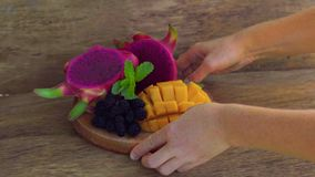 Sliced dragon fruit and mango on an old wooden background. Camera pans right stock video footage