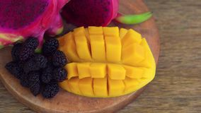 Sliced dragon fruit and mango on an old wooden background. Camera pans right stock video