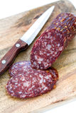 Sliced dry sausage and knife. Stock Image