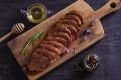 Sliced duck breast, lavender honey and rosemary on serving board. Sliced duck breast, lavender honey and rosemary on serving board royalty free stock images