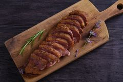 Sliced duck breast, lavender honey and rosemary on serving board. Sliced duck breast, lavender honey and rosemary on serving board royalty free stock image
