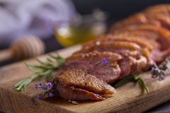 Sliced duck breast, lavender honey and rosemary on serving board. Sliced duck breast, lavender honey and rosemary on serving board stock photo