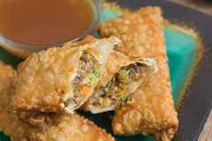 Sliced egg rolls with sauce. Sliced egg rolls sit on top of whole egg rolls with sauce in the background Royalty Free Stock Images
