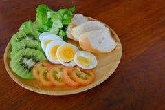 Sliced egg salad serve with vegetable, kiwi, tomato, and crispy bread Stock Photo