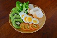 Sliced egg salad serve with vegetable, kiwi, tomato, and crispy bread stock image