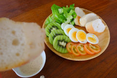 Sliced egg salad served with vegetable, kiwi, tomato, crispy bread, separated sesame dressing, and bread as foreground stock photo