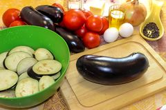 Sliced eggplant on a cutting board and soaked in salted water in. A bowl. Fresh vegetables for cooking light dinner, Moussaka - a traditional Greek dish step by Stock Photo